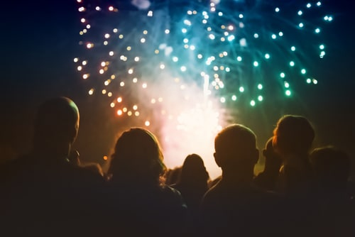 Spectators look on toward colorful fireworks
