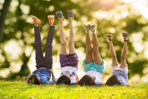 Kids Lie On The Grass With Feet In The Air