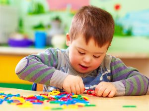 Child assembles crafts at table