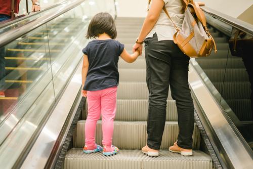 Mom And Daughter Ascend Escalator