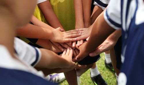 Young sports team rally with hands together