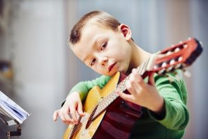 Young boy plays guitar