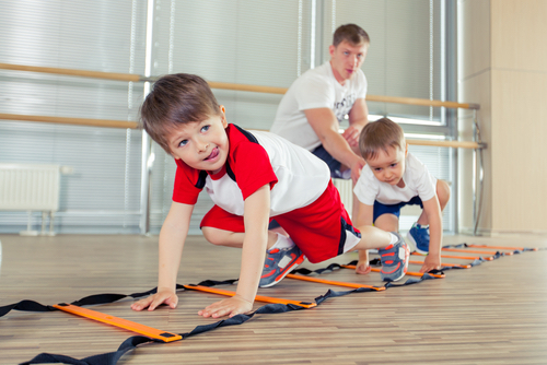 Dad Supervises Young Sons Crawling
