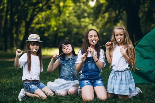 Four girls roast marshmallows at camp