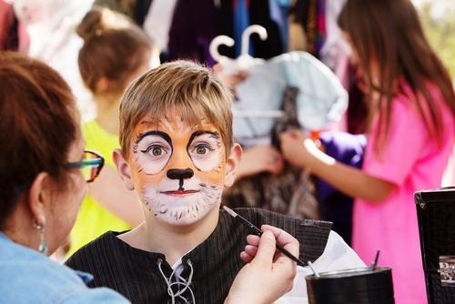 Makeup professional paints childs face like a cat
