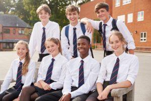 Seven uniformed kids pose at school
