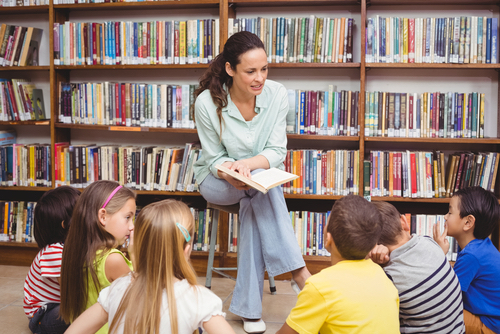 Adult Reading Book To Seated Children